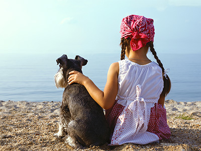 girl and dog at the beach