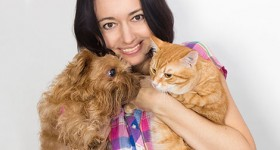 Woman holding a cat and a dog
