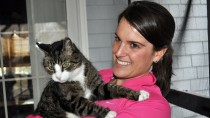 Woman holding reluctant cat