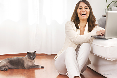 Woman laughing at computer with cat